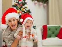 Het mamma en eet gesmeerd babymeisje in de hoeden van Kerstmis Royalty-vrije Stock Fotografie