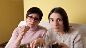 Het mamma en haar dochter eten spaanders terwijl het drinken van TV en drinken kola Comfortabele atmosfeer thuis stock video