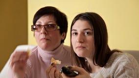 Het mamma en haar dochter eten spaanders terwijl het drinken van TV en drinken kola Comfortabele atmosfeer thuis stock footage