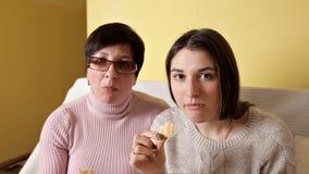 Het mamma en haar dochter eten spaanders terwijl het drinken van TV en drinken kola Comfortabele atmosfeer thuis stock videobeelden