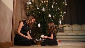 Het mamma en haar dochter laten de linten van de Kerstmisgift onder de boom in de woonkamer van hun huis los stock video