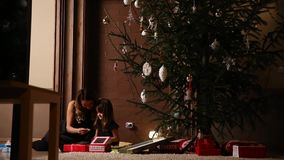 Het mamma en haar dochter laten de linten van de Kerstmisgift onder de boom in de woonkamer van hun huis los stock footage