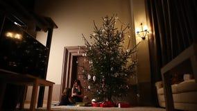 Het mamma en haar dochter openen samen Kerstmis huidig onder de boom in de woonkamer van hun huis stock footage
