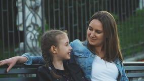 Het mamma en haar dochter zitten en spreken stock video