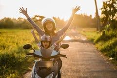 Het mamma en haar kind genieten van berijdend motorfietsautoped stock foto's