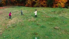 Het mamma en haar kinderen spelen met de bal in de herfst bos zij in werking gestelde pret en werpen elkaar een bal De familie is stock videobeelden