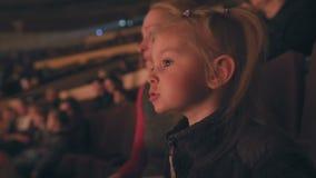 Het mamma en haar weinig dochter letten op prestaties bij het circus, vreugdevol slaand hun handen stock videobeelden