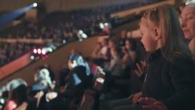 Het mamma en haar weinig dochter letten op prestaties bij het circus, vreugdevol slaand hun handen stock footage