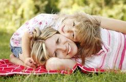 Het mamma en haar weinig dochter liggen op het gras royalty-vrije stock afbeelding