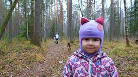 Het mamma en haar weinig dochter lopen de hond in het vochtige de herfstbos stock video