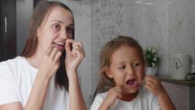 Het mamma en weinig dochter borstelen hun tanden samen met tandzijde bij badkamers stock videobeelden