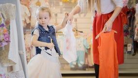 Het mamma geeft haar dochterhangers met kleren in een opslag van de kinderen` s kleding Stock Fotografie