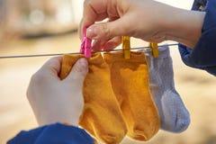 Het mamma hangt babysokken op een drooglijn voor het drogen royalty-vrije stock afbeelding