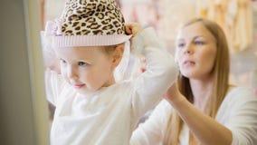 Het mamma helpt haar dochterslijtage een hoed Stock Afbeeldingen