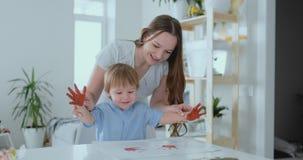 Het mamma helpt haar zoon om een handprint op papier te maken gebruikend verf Gezamenlijke vrije tijdskwestie van het kind Gelukk stock footage
