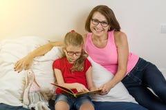 Het mamma helpt me een boek aan mijn kleine dochter lezen _zij leren laten stock afbeelding