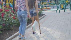 Het mamma helpt mijn dochter met een gebroken been op steunpilaren om langs de straat te lopen stock videobeelden