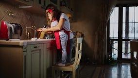 Het mamma helpt om de handen van zijn dochter in de keuken te wassen na het koken van diner stock video