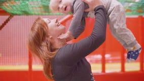 Het mamma houdt blonde zoon in handenbesprekingen, speelt met zijn neus, toen kussen en zij lachen stock video
