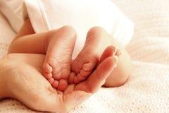 Het mamma houdt de benen van leuke pasgeboren weinig baby royalty-vrije stock foto