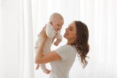 Het mamma houdt een baby op de achtergrond van het wapensvenster Stock Fotografie