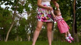 Het mamma houdt haar dochter door handen en schudt haar, gelukkige kindlach Weinig dochter die met haar moeder op groen spelen stock videobeelden