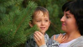 Het mamma houdt Haar Opgewekt Little Boy in Haar Wapens, achtervolgen zij Zijn Papa rond Kerstboom stock footage