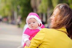 Het mamma houdt op hand een klein kind Stock Afbeelding