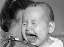Het mamma kalmeert baby de baby schreeuwt Stock Foto's