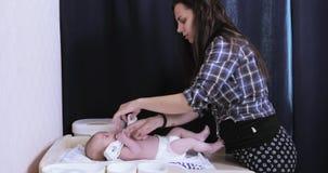 Het mamma kleedt de baby stock footage