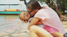 Het mamma koestert en kust haar weinig dochterzitting in hangmat op oceaanstrand stock videobeelden