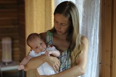 Het mamma koestert haar baby in haar wapens stock foto's