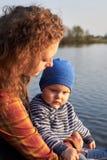 Het mamma koestert haar zoon op de pijler op de rivier royalty-vrije stock fotografie