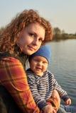 Het mamma koestert haar zoon op de pijler op de rivier stock foto