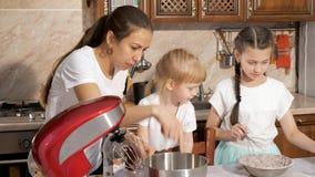 Het mamma kookt met haar twee dochters in de keuken stock video