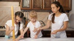 Het mamma kookt pastei van deeg met haar twee dochters in de keuken stock video