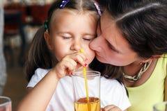 Het mamma kust haar weinig dochter Stock Foto's