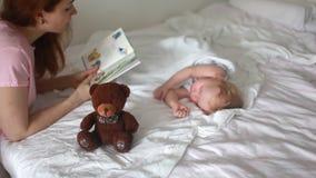 Het mamma leest een sprookje aan een kind stock video