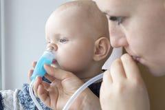 Het mamma maakt de neus van de baby schoon gebruikend een neusaspirator royalty-vrije stock afbeeldingen