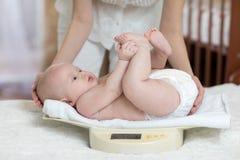 Het mamma meet baby weegt thuis op schalen stock afbeeldingen