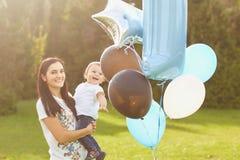Het mamma met ballons wenst haar zoon met zijn verjaardag in het park geluk stock fotografie