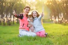 Het mamma met dochter en de hond tonen duim in de lentepark royalty-vrije stock fotografie