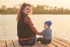 Het mamma met haar zoon zit op de pijler op de rivier, gestemde foto royalty-vrije stock afbeelding