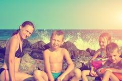 Het mamma met kinderen op het overzees op het overzees op het strand, het water slaat op de stenen Gestemde uitstekende foto royalty-vrije stock afbeelding