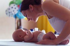Het mamma met leuke glimlach behandelt haar pasgeboren jongen op baby veranderende lijst stock afbeeldingen
