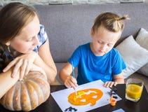 Het mamma met zoon trekt een pompoen voor Halloween Royalty-vrije Stock Afbeeldingen