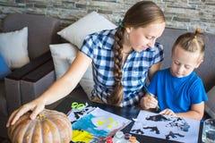 Het mamma met zoon trekt een pompoen voor Halloween Stock Fotografie