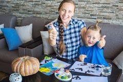 Het mamma met zoon trekt een pompoen voor Halloween Stock Foto
