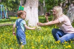 Het mamma neemt beelden van de baby in het Park royalty-vrije stock afbeeldingen