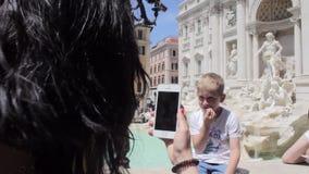Het mamma neemt beelden van haar zoon op de fontein stock videobeelden